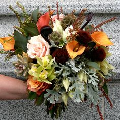 Brides.com: . Arrangement of roses, succulents, calla lilies, scabiosa pods, cymbidium orchids, dusty miller, seeded eucalyptus, foliage, and fiddlehead ferns. Bouquet by Not Just Flowers Photo: Courtesy of Not Just Flowers