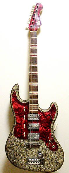 """Hofner Galaxie. Covered in vinyl with mother-of-toilet-seat tortoise pickguard, tortoise headstock, and crazy-ass tortoise-and-pearloid stripe position markers. Roller volume controls, one for each pickup, and a master tone roller. Three staple-tops. Such """"deluxe"""" appointments (and those Humbuckers) take a guitar that started out as a poor-man's Stratocaster into what Lord Buckley used to refer to as """"the great cathedral-head of BEAUTY.""""     This is the stuff, this is."""
