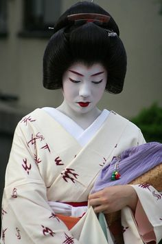 A geiko of Kyoto, her wig is called a katsura. Her collar is plain white, and kimono plain compared to a maiko.
