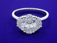 """Diamond ring with 1.22-carat oval brilliant cut diamond graded F color, SI1 clarity, depth 65.5%, table 55%, Excellent polish, Very Good symmetry, No fluorescence, and measuring 8.46 x 5.86 x 3.84 mm, 1.44 ratio (ref: GIA 17456703, laser inscribed """"GIA 17456703"""", dated 07/11/2008) prong-set in a custom 14 karat white gold three-stone mounting stamped (""""14"""") with a pair of matching crescent half moon shaped diamonds graded E color, VS2/SI1 clarity, measuring 6.2 x 3.7 mm and 1.95 mm wide…"""