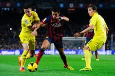 Alexis Sanchez of FC Barcelona duels for the ball with Hernan Perez (L) and Tomas Pina of Villarreal CF of Villarreal during the La Liga match between FC Barcelona and Villarreal CF at Camp Nou on December 14, 2013 in Barcelona, Catalonia.