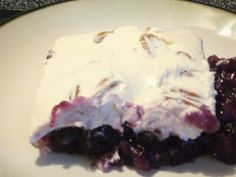 Paula Deen Blueberry Salad  Mix together 2 3-oz grape gelatin mix,2 cups boiling water,1 can blueberry pie filling,1 20-oz Crushed pineapple with juice.  Pour into a 13x9 inch shallow baking dish.  Chill for 4 hours.  Stir together 1 8-oz cream cheese,              1 cup sour cream, 1 cup pecan halves and 1 tsp vanilla.  Spread over the jelled salad.  Chill for an additional hour.