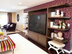 This living room is enhanced with the purple wallpaper behind the built-in entertainment center.