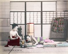 1890's. Two Half-Nude Japanese Women. A woman is sleeping on a futon, while another woman is smoking a kiseru (煙管) pipe. Both of the women are bare-breasted. A tobbaco tray, books and a fan lay on the floor in front of them, an Andon lamp can be seen behind them.
