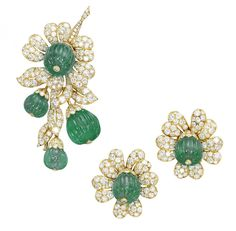 A SET OF EMERALD AND DIAMOND 'FUSCHIA' JEWELLERY, BY VAN CLEEF & ARPELS.  Comprising a brooch designed as a pavé-set diamond spray accented by four emerald fluted beads; and a pair of ear clips en suite, made in 1962, brooch 7.5 cm long, ear clips 3.0 cm long, with French assay mark for gold  Signed Van Cleef & Arpels, brooch no. 94010 and ear clips no. 94883