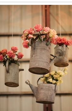 Hanging Watering Cans of Flowers - maybe have old tin oiling cans with flowers for the Wizard of Oz theme