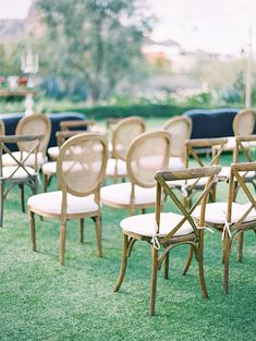 outdoor wedding ceremony with sofas and a mix of wooden chairs