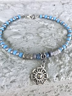 This pretty summer boho style Anklet is made with pale blue glass beads, silver glass beads, gray wood beads, blue Czech glass beads, silver tibetian beads, and a silver plated sun charm. Ankle Bracelet comes in several sizes, just choose your size from the drop down menu at