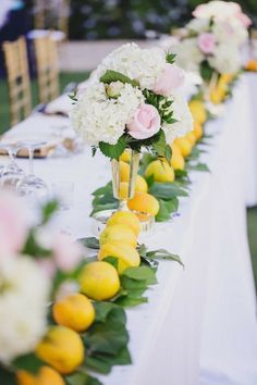 Amazing long table with header of lemon leaves and lemons and neutral setting