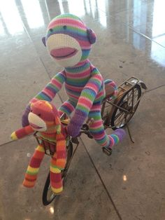 Pier 1 Rainbow Sock Monkey on his new bike with Mini Rainbow Sock Monkey