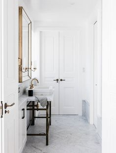 marble floors and a brass mirror