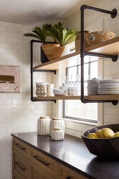 black counters, white subway tile, wood cabinets + shelves