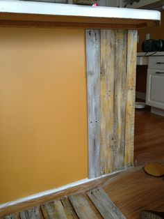 """A plain peninsula backing is fitted with painted pallet boards for a rustic element. A standard 36"""" high peninsula or island is the perfect height for utilizing the pallet boards, which average 40""""."""