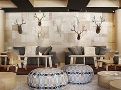 Love the layered birch paneled walls, mosaic of faux antelope heads and fun poufs.
