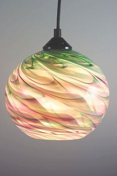 A delightful pendant light giving you two distinct colors while on or off.  CX Optic Globe Pendant by Mark Rosenbaum. Art Glass Pendant Lamp available at www.artfulhome.com