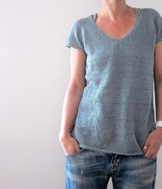 Edie is a simple tee worked with raglan increases from the top down. First you have to work back and forth until V-Neck shaping is complete, then in the round to the end. Textured stripes will help to compensate the yarns tendency to bias. Short-row shaping for the rounded bottom gives a casual finish. Stitches for short sleeves are picked up after body is complete, to work the sleeves top down in the round. An optional neck finishing is provided. Sample shows unfinished, raw edges.Yarn 5…