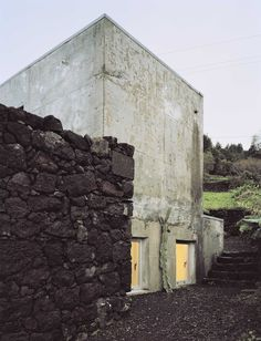 The concrete structure was designed to fit within the existing dark volcanic rock walls. Tagged: Exterior, Concrete Siding Material, and House Building Type. Photo 16 of 19 in Rising From the Ruins: Homes Built on Architectural Remains. Architecture Résidentielle, Contemporary Architecture, Futuristic Architecture, Architecture Wallpaper, Contemporary Design, Stone Facade, Concrete Houses, Concrete Siding, Clean Concrete