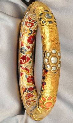 Gold and Enamel Gem-set Bangle, India, set with various foil-back cabochons, the interior with fine floral and foliate polychrome enamel, interior cir. 7 in.