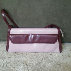 Nine West Purse Love and maroon in color. Slightly more purple than picture 1. Please note the stuff along the bottom as seen in picture 3. Otherwise in excellent condition. Nine West Bags
