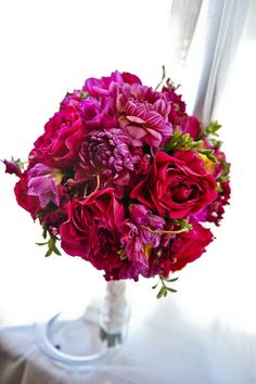 Red bridal bouquet Bold Blooms of David Austin Scarlett Roses, Fuchsia Freesia, Dahlias, and Lisianthus created this lush look for the Maid of Honor Bouquet