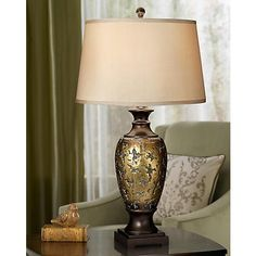 Finished in a distressed bronze, this urn shaped table lamp is topped with a beige shade.