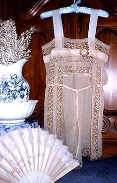 This 1920s undergarment is lavishly ornamented with lace inserts and a pretty boutonniere of silk ribbon flowers.