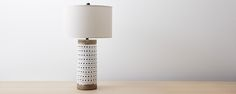 Parts of this table lamp were left intentionally unglazed to expose the natural terra cotta base. A white crackle finish covers the rest of the perforated lamp, which is balanced by an alabaster linen shade and topped with a black ceramic finial.