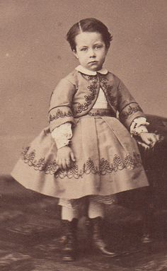 The child is beautifully dressed, but whatta sad little face!