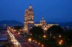 La Catedral de Morelia, Mich.Mexico. Morelia (de 1545 a 1828, Valladolid) es una ciudad mexicana, capital del estado de Michoacán de Ocampo y cabecera del municipio homónimo. La ciudad está situada en el valle de Guayangareo, formado por un repliegue del Eje Neovolcánico Transversal, en la región norte del estado, en el centro-occidente del país.  Morelia es la ciudad más poblada y extensa del estado de Michoacán y la vigésima séptima a nivel nacional, con un área de 78 km² y una población…