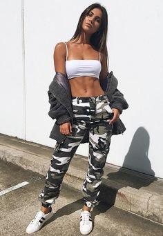 Calça cargo: mais uma trend militar que voltou com tudo. Top faixa branco, calça com estampa camuflada e bolsos, tênis branco