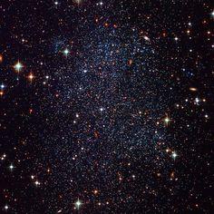 A vizinha galáxia irregular anã do Sagitário. Tem aproximadamente 1,500 anos-luz de diâmetro e encontra-se a 3.5 milhões de anos-luz da Terra, na direcção da constelação de Sagitário. Crédito: Hubble Heritage Team (AURA / STScI), Y. Momany (U. Padua) et al., ESA, NASA