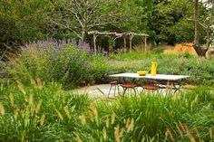 bluestone patio, dense plantings and rustic pergola, by  Oehme van Sweden (in East Hampton, NY)