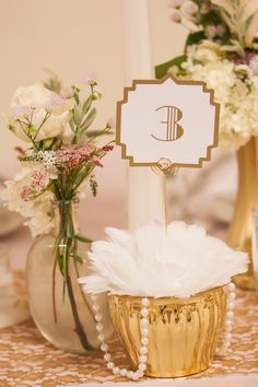 Part of our table centerpeices - vintage pearls, feathers, pink and gold inspired