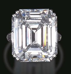 A MAGNIFICENT SINGLE-STONE DIAMOND RING, BY HARRY WINSTON  Set with a rectangular-cut diamond, weighing approximately 26.74 carats, flanked on either side by tapered baguette-cut diamonds, mounted in platinum With jeweler's mark for Harry Winston