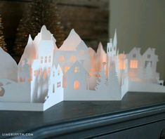 Paper Cut Winter Village for your Holiday Decorations DIY - Paper cut Winter Village. This winter village has a mountain scape in the background with little village houses, clock towers, light poles and trees in the front two layers. The cut also features Noel Christmas, Christmas Paper, All Things Christmas, Winter Christmas, Christmas Ornaments, Diy Paper, Paper Crafts, Cut Paper Art, Paper Toys