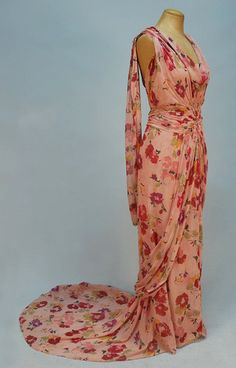 TRAINED PRINTED CHIFFON EVENING GOWN, 1930's. Sleeveless pink silk with a stylized floral in red, pink, plum, green and yellow, cowl neck bodice with central ruched sunburst midsection forming sash with chiffon covered wooden ring closure at back and long swag on skirt back, rings at shoulders joined by a second long swag, curved train. Front