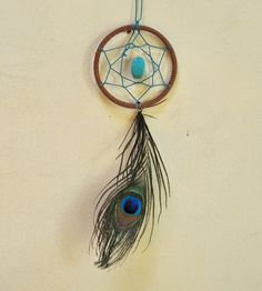 Peacock Feather Car Dash Dream Catcher    Spice up your rear view mirror with the Reina Peacock Feather Car Dash Dream Catcher! Features include a