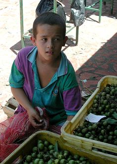 A boy selling mamones at the open market in San Cristobal, Venezuela. www.andeanaid.org