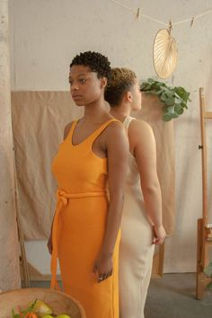 Knit mid-calf tank dress with low scoop back and matching rope belt, in Tangerine. Available in S/M and L/XL. CARE: Pre-treat any stains, hand wash gently in hot water, and air dry. Or wash on gentle cycle and tumble dry. photographer: Alexis Paschal models: Juell Towns (wearing the S/M) and Josella Baird