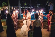 Guests Hold Sparklers Around Couple |   Photography: Juan Carlos Tapia Photography.   Read More:  http://www.insideweddings.com/weddings/rustic-destination-wedding-with-touching-details-on-beach-in-mexico/801/