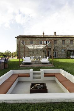 Garden - White seating areas against stone walls at La Bandita, in Tuscany