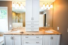 A traditional double vanity features white cabinetry and neutral stone countertops. Mirrors from the backsplash to the ceiling help expand the space.