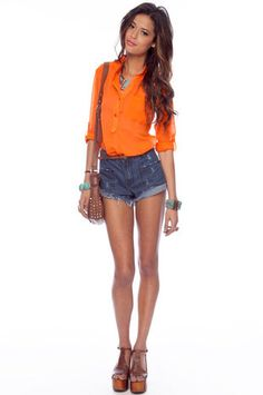 loose orange blouse, turquoise jewelry, denim shorts, brown leather bag, and shoes. easy summer chic.
