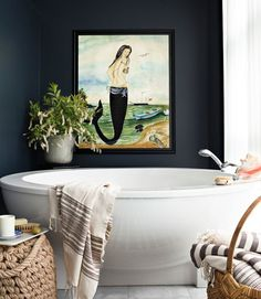 Love everything about this bathroom! The navy walls, giant soaking tub, mermaid painting, Turkish bath towels, rope ottoman...everything!