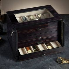 Securely store and display your fine wristwatches in our lockable Italian Ebony Watch Chest. The handmade, polished ebony case holds 28 watches on holders and in trays, displaying your favorites via a glass top.Handmade in Florence, Italy by Agresti artisansIncludes four drawers with leather handlesFeatures a luxurious antique-white, tarnish-resistant ultrasuede interiorHandmade and shipped from Italy; please allow approximately 8 weeks for delivery