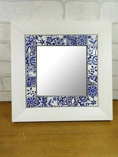 Decorative wall mirror with blue and white mosaic tiles.