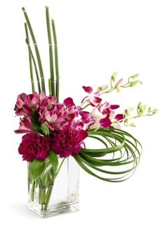 Fuchsia Dendrobium #Orchids, purple Alstroemeria and purple #Carnations showcase this cosmopolitan design. Equisetum and Lily grass accent this graceful bouquet that's arranged in a contemporary glass vase.  #StyleMeChalkboardBride