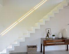 Moderne witte trap in Corian met leuning langs de muur met ingebouwde led verlichting