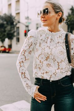 fashion blogger wearing long sleeve white lace top dark wash skinny jeans with oversized square sunglasses