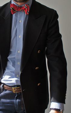 Double-breasted navy jacket, light blue shirt, red bow tie with yellow & blue stripes